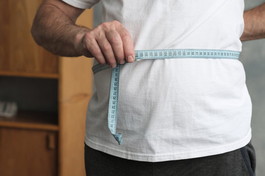 Fat mature man measuring his belly with measurement tape standing in the living room. Problem with overweight, bad health and dieting concept