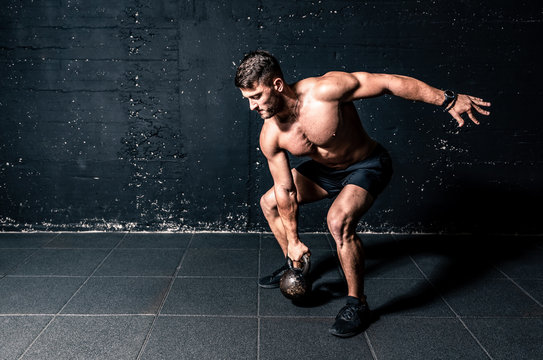 Young strong sweaty focused fit muscular man with big muscles holding heavy kettle bell for training hard core workout in the gym real people
