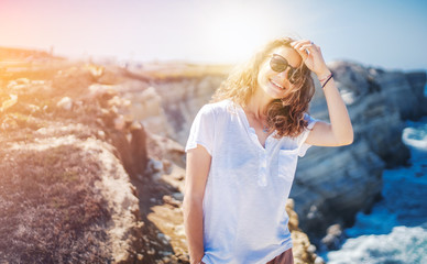 Wall Mural - Beautiful young woman with a happy smile in a white T-shirt on the ocean in Portugal, travel and relax
