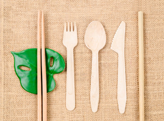Wooden spoon set and straw bamboo tube on sack background.