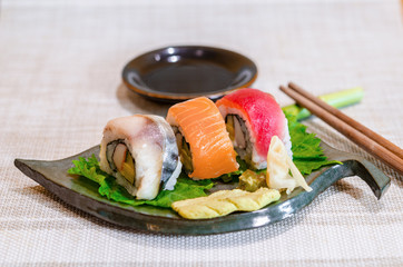 Sushi roll with salmon, Tuna on leaf dish.