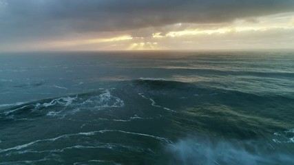 Wall Mural - Aerial view on big waves of Atlantic ocean and dramatic sunset sky, 4k