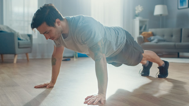 Strong Athletic Fit Man in T-shirt and Shorts is Doing Push Up Exercises at Home in His Spacious and Bright Living Room with Minimalistic Interior.