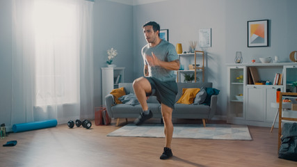 Strong Athletic Fit Man in T-shirt and Shorts is Energetically Jogging in Place at Home in His Spacious and Bright Living Room with Minimalistic Interior.