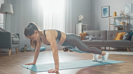 Strong Confident Beautiful Fitness Girl in Grey Athletic Sportswear is Doing Push Up Workout Exercises in Her Bright and Spacious Apartment with Cozy Minimalistic Interior.
