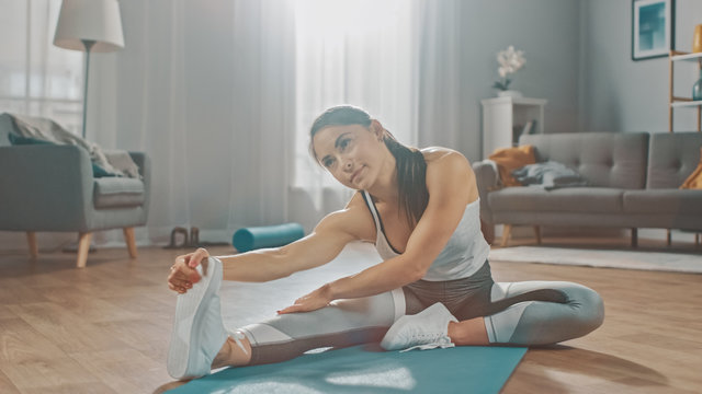 Beautiful Confident Fitness Girl in an Athletic Workout Clothes is Doing Stretching Yoga Exercises in Her Bright and Spacious Living Room with Cozy Modern Interior.