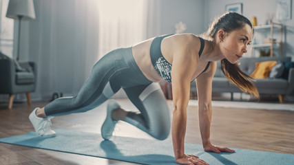 Profile Shot of a Beautiful Confident Strong Fitness Female in a Grey Athletic Outfit Doing Mountain Climber Exercises in Her Bright and Spacious Apartment with Cozy Minimalistic Interior.