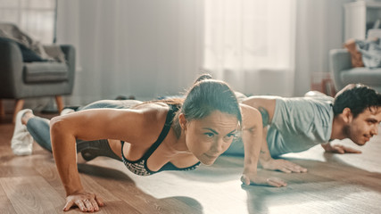 Muscular Athletic Man and Beautiful Fitness Woman in Workout Clothes Doing Push Up Exercises in Their Bright and Spacious Living Room with Minimalistic Interior.