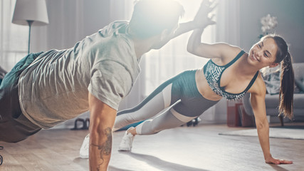 Smiling Strong and Beautiful Athletic Fitness Couple in Workout Clothes Doing Push Up Exercises and...