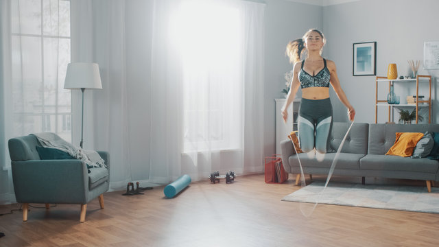 Strong and Fit Beautiful Girl in an Athletic Top Energetically Exercises With Jump/Skipping Rope in Her Bright and Spacious Living Room with Minimalistic Interior.