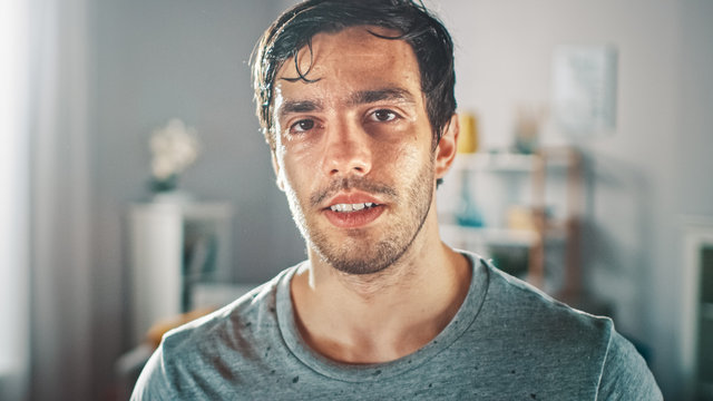 Sweating Muscular Athletic Fit Man in Grey Outfit is Posing After a Workout at Home in His Spacious and Sunny Living Room with Minimalistic Interior.