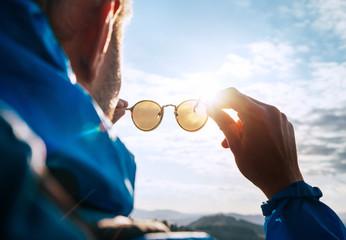 Backpacker man looking at bright sun through polarized sunglasses  enjoying mountain landscape. Eye...