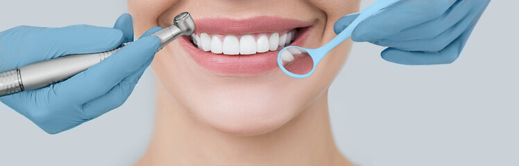 Cropped perfect smile and dentist hands holding a dental drill and an angle mirror. Dentistry and...