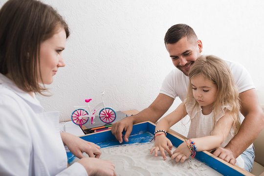 Sand therapy as a way of mental therapy and treatment of children. psychiatrist, doing sand therapy with child and her parent