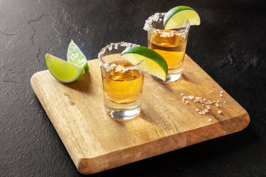 Golden tequila shots with lime slices and salt rims on a black background