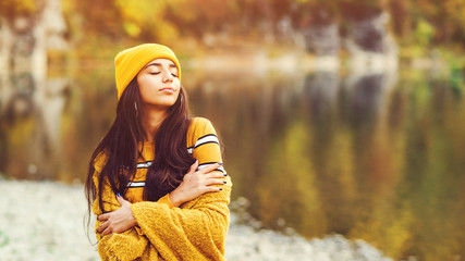 Foto auf AluDibond Orange Beauty and fashion. Romantic woman in autumn. Pretty tenderness girl wearing warm autumn clothes, hat and yellow scarf. Girl enjoing autumn day