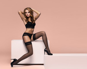 Fashion model posing in erotic underwear. Woman in beautiful lingerie over colored background.