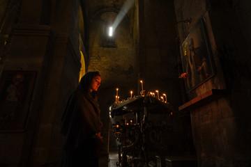 Young woman?praying near icon