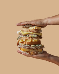 The hands of the men hold a large sandwich made from different cheese and different healthy bread with sesame seeds on a light brown background with copy space.