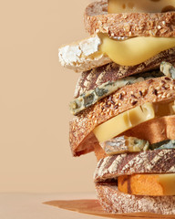 Closeup of a freshly made healthy sandwich of cheese and slices of bread with flax and sesame seeds on a light brown background with copy space.