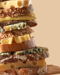 Different pieces of cheese and homemade bread with sesame and flax seeds. Diet sandwich presented on a light brown background with copy space close-up.