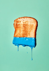 A piece of fried toast painted blue presented on a green background with splashes and copy space.