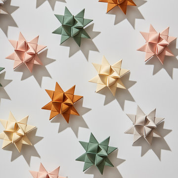 Beautiful pattern of a variety origami paper stars on a gray background with shadows. Holiday composition. Flat lay