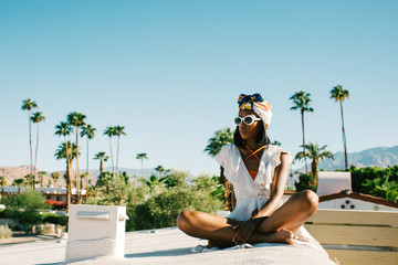 Young Beautiful Black Fashionista Sitting on California Hotel Rooftop