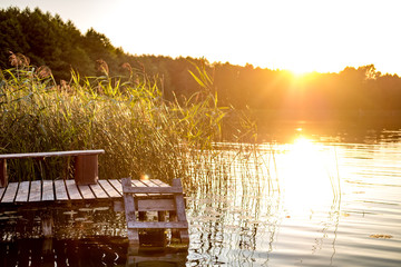 panorama on huge lake or river near wooden pier in evening with beautiful awesome sunset