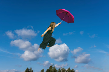 Cute girl jumping funny in clouds above earth. Small cheerful girl walking through sky with pink umbrella. Levitation concept