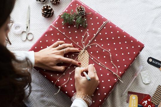 Writing christmas gift tag.