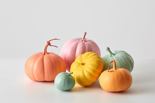 Halloween creative handmade painted pumpkins in a various colors isolated on a white background with copy space. Greeting card