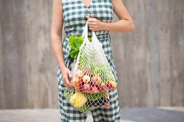 Woman walking and shopping fruits and vegetables with reusable cotton Eco produce bag. Zero waste lifestyle concept