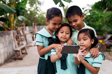 Asian schoolkids using smartphone