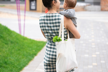 Young mother with baby son walking and shopping fruits and vegetables with reusable cotton Eco produce bag. Zero waste lifestyle concept. Concern for the next generation