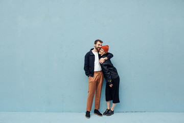 Couple having fun against the blue wall