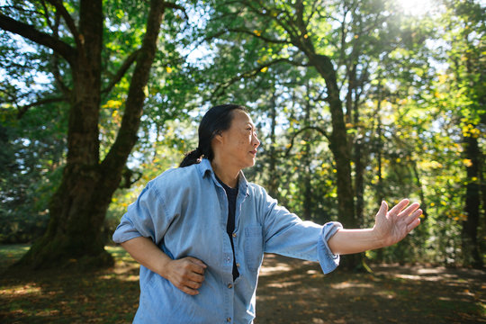Mature asian woman practicing tai chi outside.