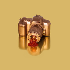 Golden SLR Camera on Gold with Drip from Lens