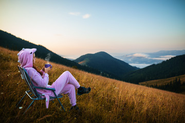 Young girl in a pink dragon costume drinking coffee while sitting in a chair on top of a mountain. Incredible mountain landscape at sunrise. Girl in pink pajamas drinks hot drink in the mountains Fototapete