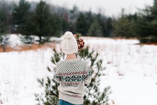 back of boy decorating a Christmas tree in the outdoors