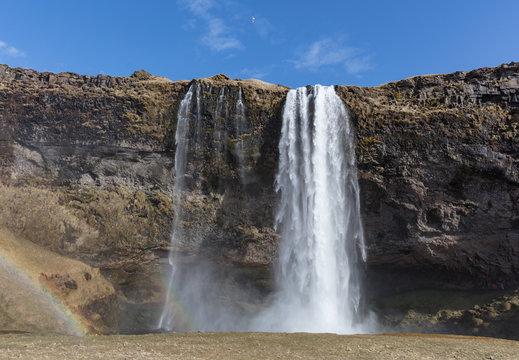 A waterfall cascades over a cliff edge.