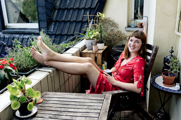 Portrait of smiling young woman relaxing with cup of coffee on balcony