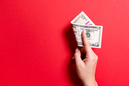 Top view of female hand holding a pack of money on colorful background. Five dollars. Business concept with empty space for your design. Charity and tips concept