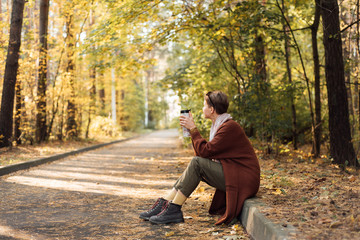Woman drinking hot beverage in autumn park