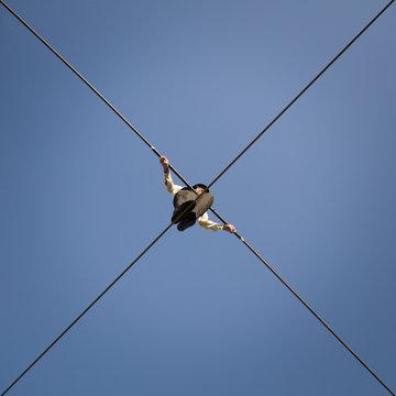 A tightrope walker seen from below