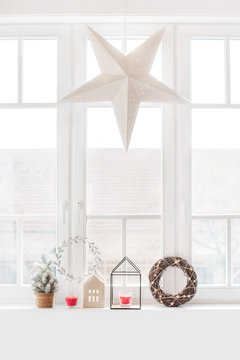 Christmas decoration on a window sill and a large paper star hung up