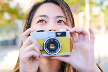 Portrait of woman taking photos with a vintage analog camera