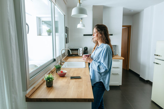 Young woman wearing pajamas in kitchen at home looking out of window