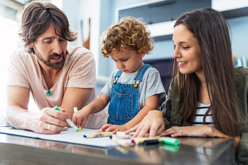 Adorable happy family drawing at home