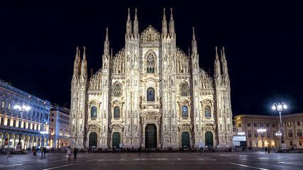 Fototapete - Milan Cathedral or Duomo di Milano at night, Italy. It is a top landmark of city. Ornate Gothic facade of the famous Milan Cathedral at dusk. Long exposure of main Milan square with blurred people.